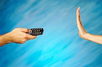 Man's hand holding a remote control with a woman's hand making a stop gesture