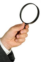 Close-up of a businessman holding a magnifying glass