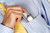 Mid section view of a businessman putting a mobile phone into his shirt pocket