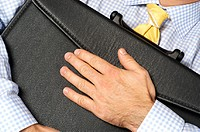 Close-up of a businessman hugging his briefcase