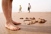 Kid's feet standing by water hole in sand, background: people walking along the beach