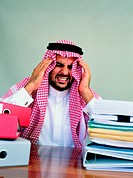 Arab businessman stressed out at his desk