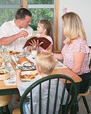 Family at Dining Table Reading Bible