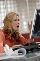 Stressed woman using desktop computer.