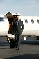 Businessman exiting private plane, portrait.