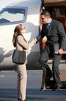 Business people shaking hands outside of airplane.