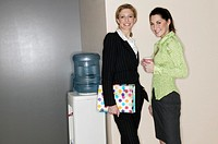 Businesswomen standing by water cooler, portrait.