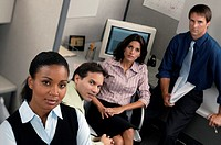 Business group in cubicle, portrait.
