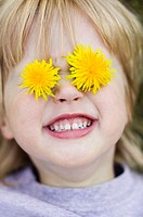 Young girl (3 yrs) with dandelions over eyes