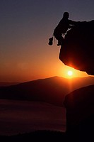 Silhouette of rock-climber at sunset