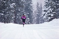 Woman jogging along road in winter