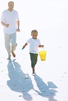 Father and son (3-5) running at beach