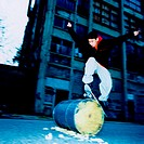 Teenage Boy Jumping an Oil Drum on a Skateboard