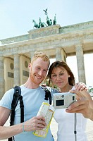 Germany, Berlin, couple taking picture by Brandenburgh Gate