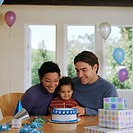 Baby boy (12-15 months) sitting with parents in front of birthday cake