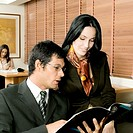 Businessman and a businesswoman sitting in an office and looking at a magazine