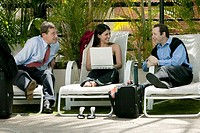 Businesswoman holding a laptop and talking with two businessmen