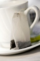 Close-up of a tea cup and a teabag in a saucer