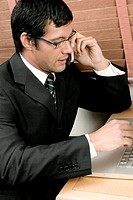 High angle view of a businessman sitting in front of a laptop using a mobile phone