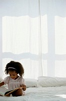 Girl (2-4) sitting on bed, looking at picture book