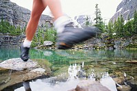 Hiker stepping on stones through stream, low section (blurred motion)