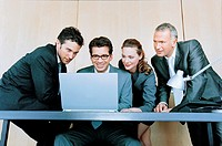 Four business people at desk looking at laptop computer screen