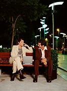 Man and woman sitting on park bench beside laptop, talking, night