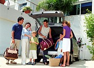 Family loading luggage in mini van