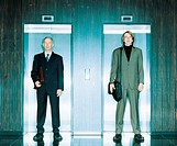 Two businessmen standing in front of elevator doors