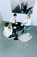 Three businessmen sitting at table, drinking espresso, elevated view