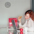 Woman using mobile phone at laptop computer whilst eating sandwich