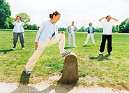 Group of mature people exercising outdoors, woman with foot on bollard