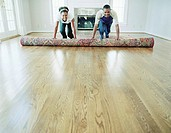 Couple unrolling area rug in living room of new home