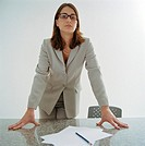 Businesswoman leaning on conference room table, portrait