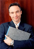 Businessman holding file, portrait, close-up