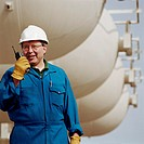 Man wearing hard hat, using walkie talkie at oil refinery