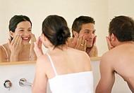 Man and woman looking in bathroom mirror