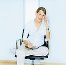 Businesswoman using mobile phone, personal organiser on lap, portrait