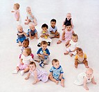 Group of babies (5-12 months) sitting on floor, elevated view