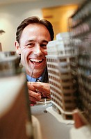 Architect looking at building model, smiling (focus on face)