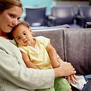 Girl (1-3) sitting on mother´s lap in hospital waiting room
