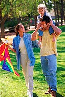 Family walking in park, carrying kite