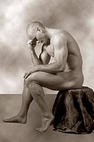Nude male posed as thinker