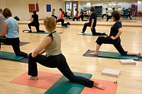 group of people in a pilates class, kneeling up stretching