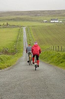 Two bikers ride down a country lane on the Isle of Skye, Scotland, UK