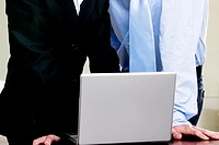 Mid section view of a businessman and a businesswoman in front of a laptop