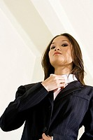 Low angle view of a businesswoman adjusting her tie