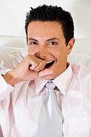 Portrait of a businessman covering his mouth with his hand while yawning