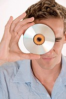 Portrait of a mid adult man peeking through a CD