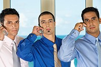 Portrait of three businessmen talking on mobile phones